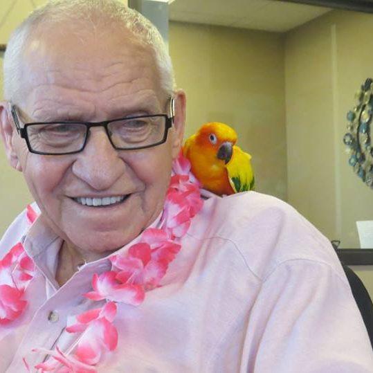 Elderly man with parrot on shoulder