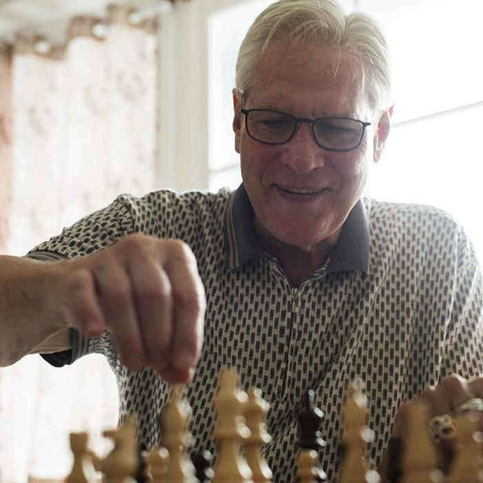 Senior resident playing chess in memory care